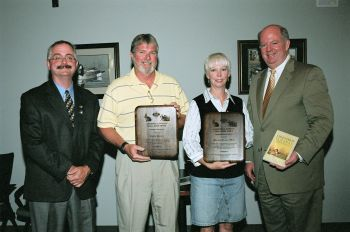 David Cobb (L), Division of Wildlife Management Chief, and Wes Seegars (R), N.C. Wildlife Commissioners Chairman, present the 2006 Larry Diedrick Small Game Awards to Ruffin Powers and Dawn Williamson of Murphy Brown LLC.