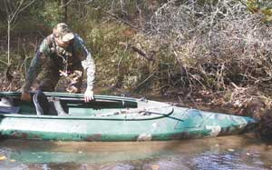 Wearing chest waders is necessary when using a float boat as hunters will frequently need to port over obstructions. Tommy Price of Anderson pulls his kayak over a logjam.