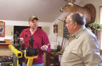 Rusty Moore of Gibsonville (left) checks and tunes up Bob Brewer�s compound bow before deer season begins.