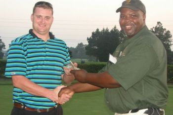 Ryan Richardson (left) accepts putting contest winnings from QDMA volunteer Steve Horton at the organization�s Crooked Creek Golf Club event.