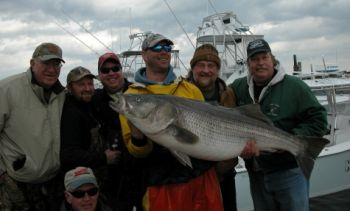 Mate Russell Long is holding the striper and angler Keith Angel is in brown behind him