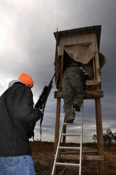 "Jason James and Trey Padgett head for an elevated ""pig"" stand that was also used for hunting deer until the deer season ended."