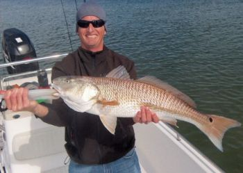 A happy angler displays a 30-plus-inch redfish caught while aboard Capt. Jeff Wolfe�s 22-foot bay boat at the lower Cape Fear bays.