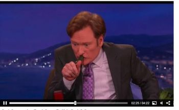 Conan O'Brien attempts to blow a duck call after receiving a lesson from Duck Commander's Phil Robertson.