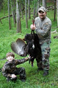 Guide B.J. Keener holds up the gobbler taken by 8-year-old Cory Holbrooks of Franklin on an April 21 hunt for handicapped kids in Macon County.