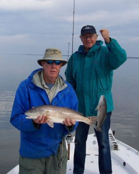 Two of Capt. Charlie Beadon's clients show off the kind of redfish biting on mud flats around Hilton Head Island.