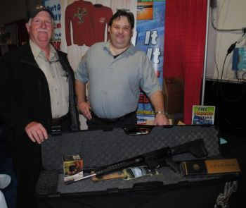 J.O. Teel of Greenville (left) shows off his winnings as grand-prize winner in North Carolina Sportsman's Bag-A-Buck contest: a Designated Marksman's Rifle from Barnes Precision Machinery and an optics package from Leupold. Matt Kozik of Barnes Precision Machine (right) helped with the presentation.