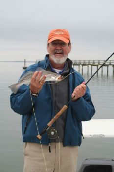 Capt. Richard Sykes shows off a speckled trout that fell for a fly.