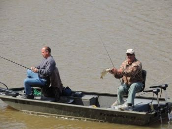 Doug McNeill fishes while Andy Futrell catches a bass from the back of the boat at Ramseur Lake this past Saturday.