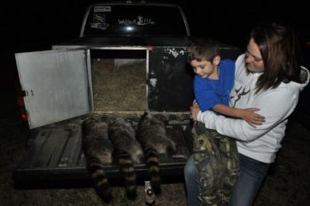 Angie Jackson and her 5-year-old son, Tucker, take in several raccoons killed on the Lumber River Outdoors/True Vince Coon Club youth hunt, which Tucker won with a 7-pound, 7-ounce raccoon.