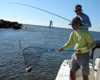 Guide Mark Stacy of Ocean Isle, N.C., nets a speck for retired guide Brandon Sauls. The fish hit a shrimp fished under a cork.