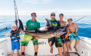 Brayden McMullan, Brant McMullan, Barrett McMullan, Dylan Stone, and Conner Yates pose with one of the recent daylight swordfish caught out of Brunswick County.