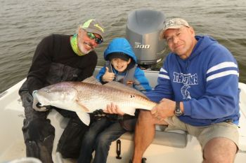 Flanked by Capt. Rod Thomas (left) and Steven Finney (right), 12-year-old Howell Brown poses with the big redfish he caught at the Georgetown jetties last Friday.