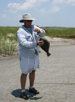 Morgan Watt puts the death grip on a flounder he caught in Fripp Island's Turtle Creek.