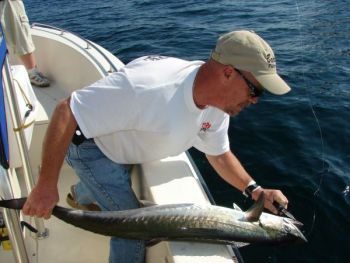 Jeff Reid of Sanford, N.C., removes a hook before releasing a spring-run king caught off Oak Island, N.C.