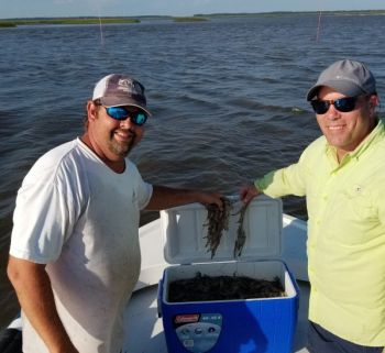 Jamie Bateman and Dalton Reames working on filling up a 48-qt cooler in St. Helena Sound in South Carolina's lowcountry.