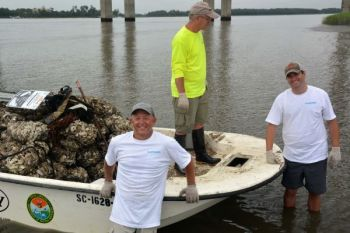 Blaine Anderson (left) and Geoff Mikota (right - in the white Shimano shirts that were no longer white at the end their efforts - get ready to help an SCDNR staffer with oyster bed restoration projects coordinated by CCA SC.