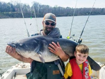 Austin Sartin (left) holds the 100-pound blue catfish that youth angler Sam Carver (right) caught at Kerr Lake.