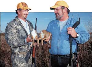 """Scott Humphrey (left) holds a swamp rabbit or """"bluetail"""" while Eddie Beck has a cottontail rabbit taken during a Hyde County hunt."""