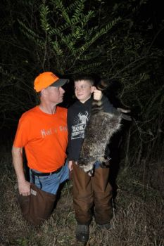 Rev. Wade Hall and 10-year-old Gage Zokal admire a raccoon taken in Columbus County, where extensive swamps and agricultural land make for great habitat.