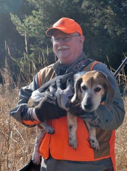 A.C. Weeks of Guilford County carries a tired beagle near the end of a day's hunt through rough terrain.