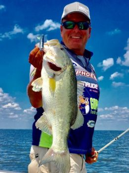 The author shows off a big, July bass that hit a Storm 360 swimbait.
