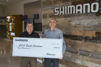 Scott Whitaker (left), executive director of CCA SC, accepts Shimano's donation from Shimano North American Fishing's vice president Steve Ferrara (right).