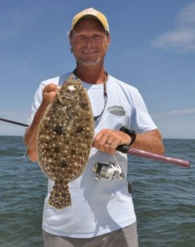 A triangle of three dark, eye-like spots identifies this flatfish as a Gulf flounder.