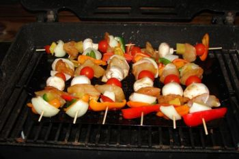 Chunks of pineapple, cherry tomatoes, bell peppers and mushrooms join skewered grouper cheeks on the grill.