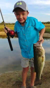Brantlee Knight poses with his first largemouth bass, a 5-pounder that he caught with a Zebco 404 and a cricket.